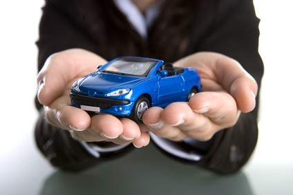businesswoman holding car in the hands - insurance or car business concept